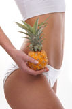 Sexy body of a young woman holding a pineapple Royalty Free Stock Images