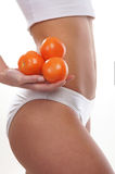 Sexy body of a young woman holding tomatoes Stock Photo