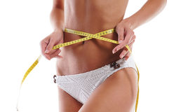 Sexy body of a young woman measuring hips Royalty Free Stock Images