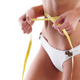 Sexy body of a young woman measuring hips Stock Photo
