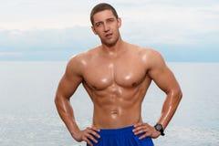 Sexy bodybuilder on the beach Royalty Free Stock Photos
