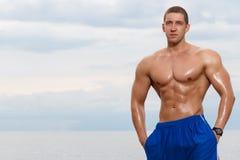 Sexy bodybuilder on the beach Stock Photos