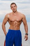 Sexy bodybuilder on the beach Royalty Free Stock Images