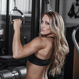 Sexy bodybuilder pulldown practice in gym. Back, shoulder and triceps exercise Stock Photo