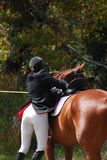 Bottoms. Showjumping team adjust saddle at gymkana stock image