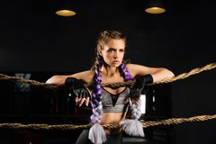 Sexy boxing girl leaned kneels on ropes of competition ring. Fashionable portrait. Sexy boxing girl leaned kneels on ropes of competition ring. Fashionable Stock Photo