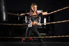 Sexy boxing girl leaned kneels on ropes of competition ring. Fashionable portrait. Sexy boxing girl leaned kneels on ropes of competition ring. Fashionable Stock Images