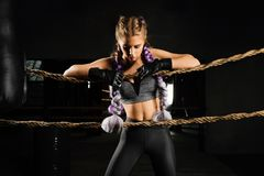 Sexy boxing girl leaned kneels on ropes of competition ring. Fashionable portrait. Sexy boxing girl leaned kneels on ropes of competition ring. Fashionable Royalty Free Stock Images