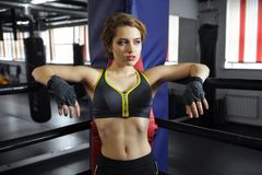 Sexy boxing girl stands leaned on ropes of competition ring. Fashionable portrait of luxurious female model Stock Photography