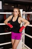 boxing girl stands leaned on ropes of competition ring. Fashionable portrait of luxurious female model. royalty free stock image