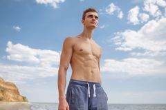 A sexy boy with a muscular torso stands on a seashore on a natural blurred background. Royalty Free Stock Photo