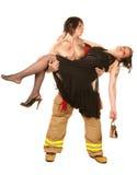 Sexy brandweerman die mooie vrouw redt Royalty-vrije Stock Foto's