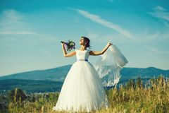 Sexy bride cute woman. Sexy bride cute happy woman with pretty face with flying wedding veil and white lace dress on sunny summer field on blue sky background royalty free stock images