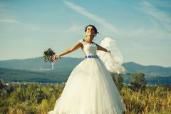 Sexy bride cute woman. Sexy bride cute happy woman with pretty face with flying wedding veil and white lace dress on sunny summer field on blue sky background stock images