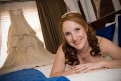 Sexy bride laying on bed with wedding dress in win Royalty Free Stock Image
