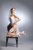 A sexy bride posing in white erotic lingerie on a chair Royalty Free Stock Images