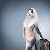 A sexy bride posing in white erotic lingerie on a chair Stock Images
