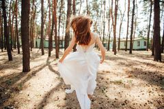 bride runs in her dress in forest stock images