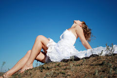 Bride sitting on the ground. Against the blue sky royalty free stock photography