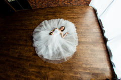 Sexy bride in the studio is lying on the wooden floor Royalty Free Stock Photos