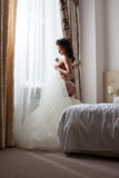 Sexy bride undressing in hotel room Stock Photo