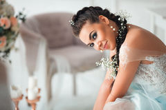 A bride in a wedding dress sitting on a chair. The girl is preparing for her wedding royalty free stock photography