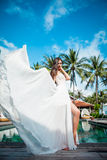 Sexy bride in white dress in luxury resort. Fashion dress fly on wind. Romantic woman relaxing near swimming pool. Stock Images
