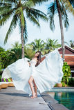 Sexy bride in white dress in luxury resort. Fashion dress fly on wind. Romantic woman relaxing near swimming pool. Royalty Free Stock Photos