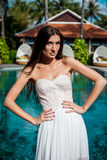 Sexy bride in white dress in luxury resort. Romantic woman relaxing near swimming pool. Royalty Free Stock Photography