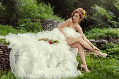 Bride woman with long legs in lush wedding dress. Bride woman with long legs in lush wedding dress sits on nature royalty free stock photography