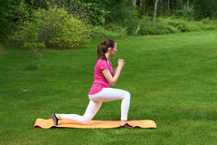 brown haired woman doing physical exercises for buttocks and legs on orange mat in outdoor on grass in nature. Royalty Free Stock Photo