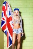 Sexy bruine kleurmeisje in korte jeansborrels tegen groene bakstenen muur Royalty-vrije Stock Foto