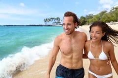 Sexy bruine kleurpaar die tussen verschillende rassen op strand lopen royalty-vrije stock afbeeldingen