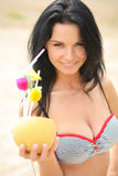Sexy brunette on the beach with a cocktail Stock Photography