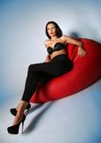 Sexy brunette Beauty sitting on a red armchair Royalty Free Stock Photography