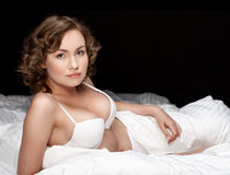 Sexy brunette in the bed in a darkened room Stock Photos
