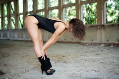 Sexy brunette in black leotard and high heels, dancing in old building. Royalty Free Stock Photography