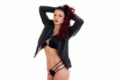 Sexy brunette in black lingerie and jacket raised her hands up and looks into the camera Royalty Free Stock Photo
