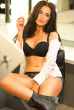 Sexy brunette in black lingerie and white shirt sitting on the v Royalty Free Stock Photos