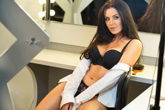 Sexy brunette in black lingerie and white shirt sitting on the v Stock Photography