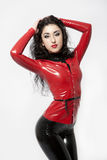 Brunette in black and red latex. Flexible brunette in black and red latex keeping her hair. Studio shot. On white background royalty free stock photo
