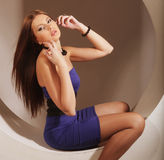 Sexy brunette in blue dress sitting in a circle Stock Photos