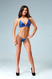 Sexy brunette bodybuilder woman in blue bikini. Sexy blond bodybuilder woman in black bikini. Posing and showing muscle on black background. The model looks at Stock Images