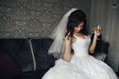 Sexy brunette bride in white dress with champagne glass. Posing on elegant couch Royalty Free Stock Photos