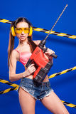 Sexy brunette builder on a blue background with an electric tool in the hands of. Builder woman in sexy clothes on a blue background holding a male construction Royalty Free Stock Image