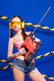 Sexy brunette builder on a blue background with an electric tool in the hands of. Builder woman in sexy clothes on a blue background holding a male construction Royalty Free Stock Photo