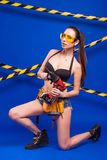 Sexy brunette builder on a blue background with an electric tool in the hands of. Builder woman in sexy clothes on a blue background holding a male construction Stock Photography