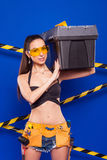 Sexy brunette builder on a blue background with an electric tool in the hands of. Builder woman in sexy clothes on a blue background holding a male construction Royalty Free Stock Photos