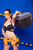 Sexy brunette builder on a blue background with an electric tool in the hands of. Builder woman in sexy clothes on a blue background holding a male construction Stock Images