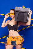 Sexy brunette builder on a blue background with an electric tool in the hands of. Builder woman in sexy clothes on a blue background holding a male construction Stock Photo